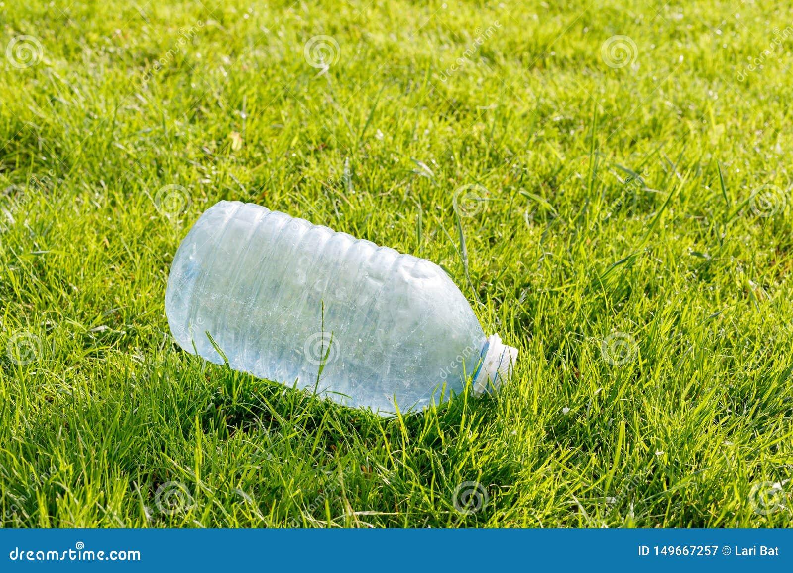 Garrafa pl?stica vazia em um gramado verde Conceito: polui??o ambiental