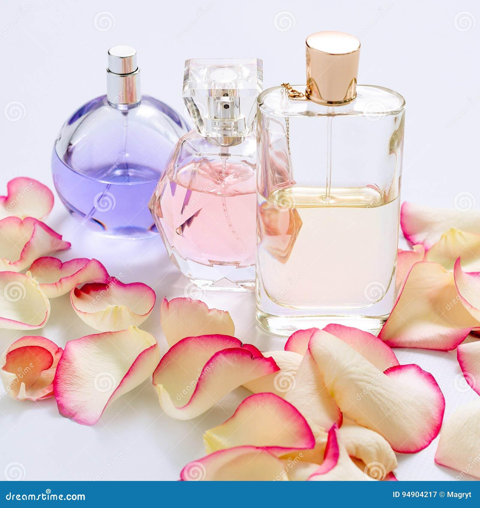 Garrafas de perfume com as pétalas da flor no fundo claro Perfumaria, coleção da fragrância Acessórios das mulheres