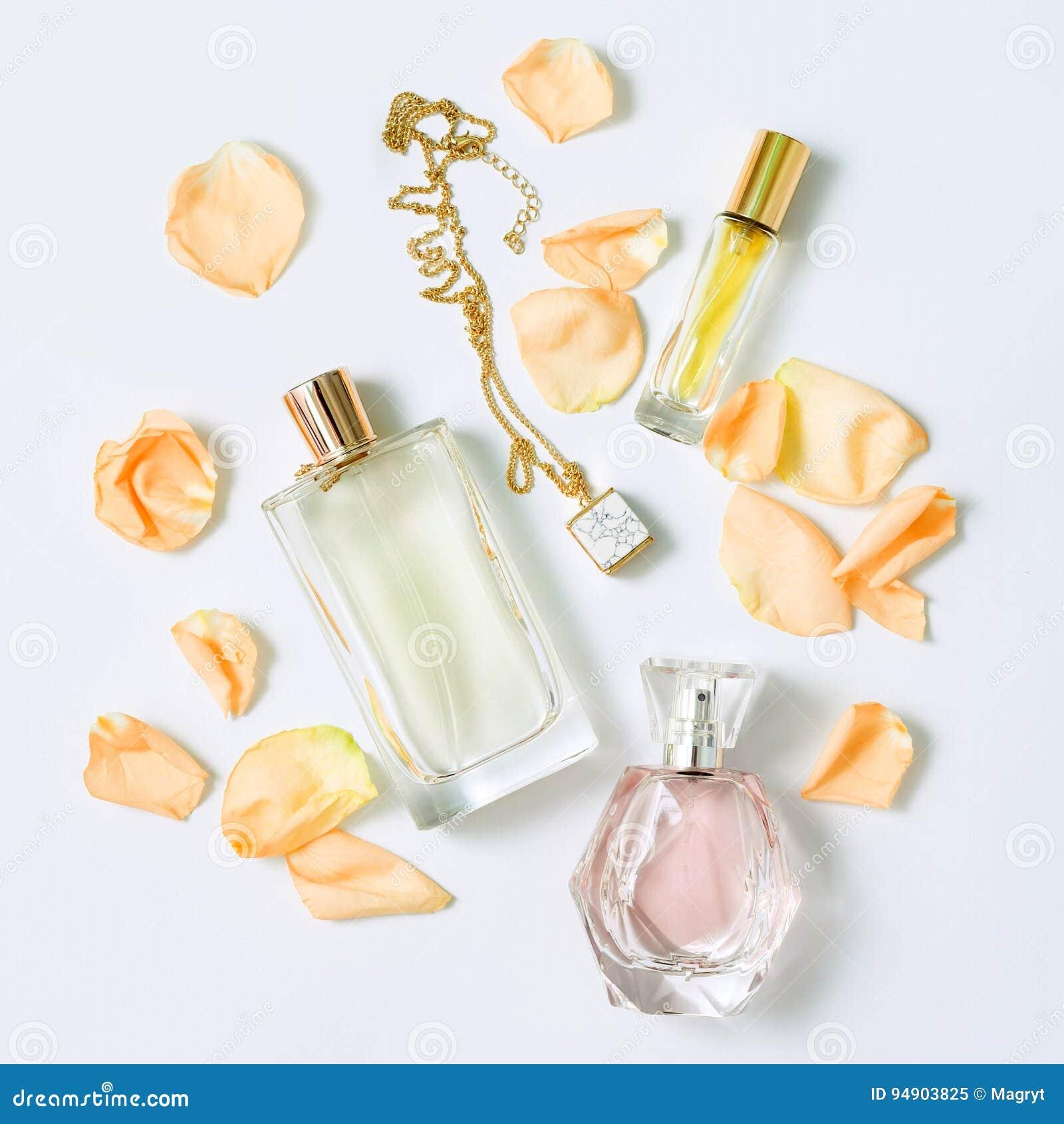 efe62c241957 Garrafas de perfume com as pétalas das flores no fundo branco Coleção da  perfumaria, dos cosméticos, da joia e da fragrância Flatlay feminino  estilizado ...