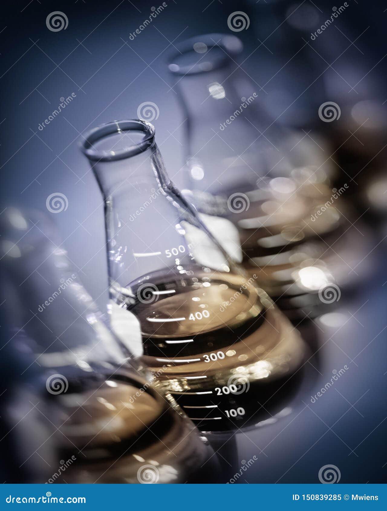 Garrafas do laboratório do foco seletivo com soluções do ouro amarelo