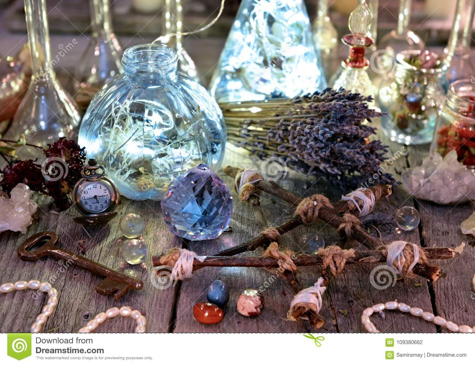 Garrafas mágicas com luzes, pentagram, cristal e objetos do ritual na tabela da bruxa
