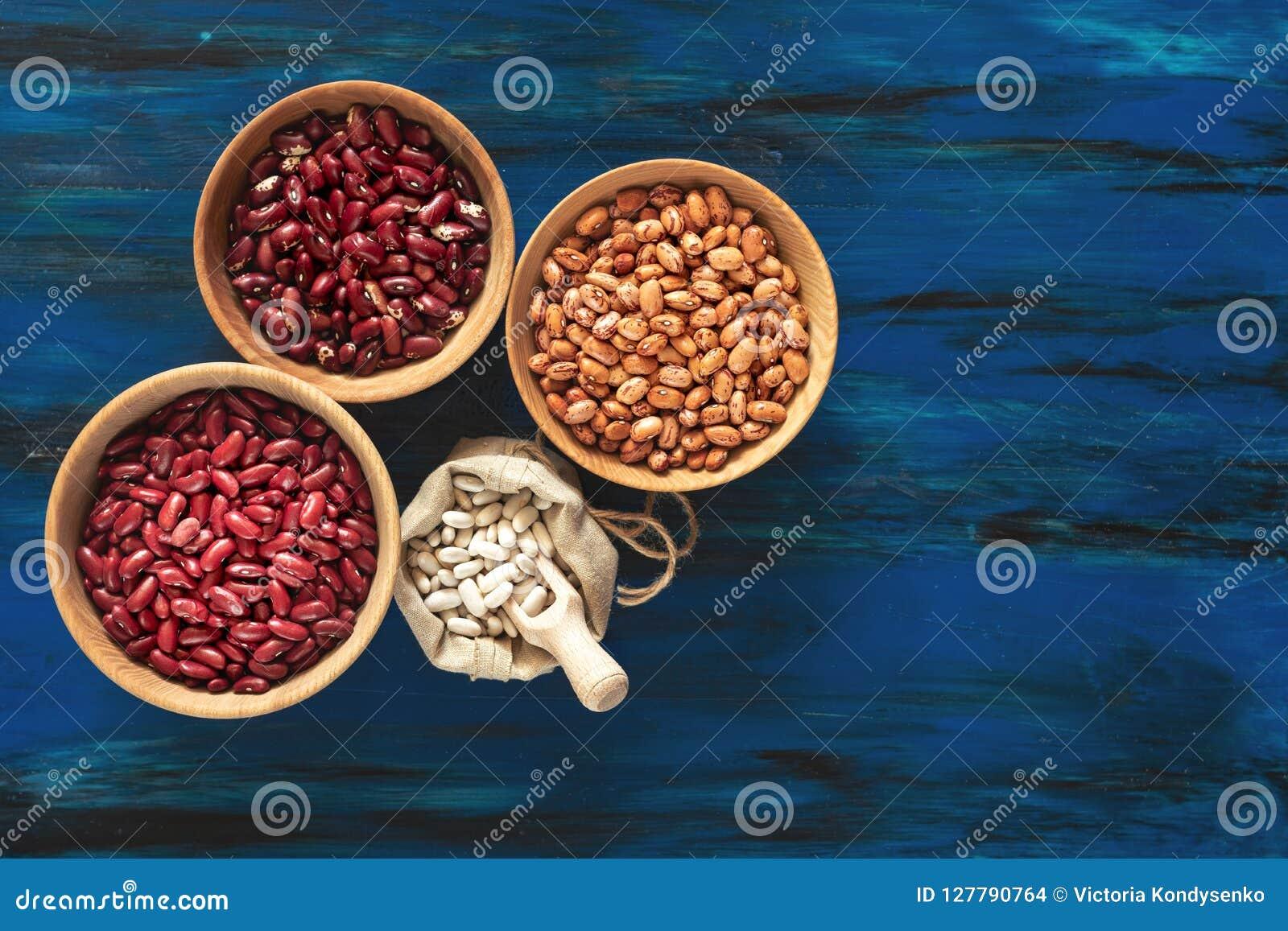 Gartenbohnen in den hölzernen Tellern und weiße Bohnen im Leinenba