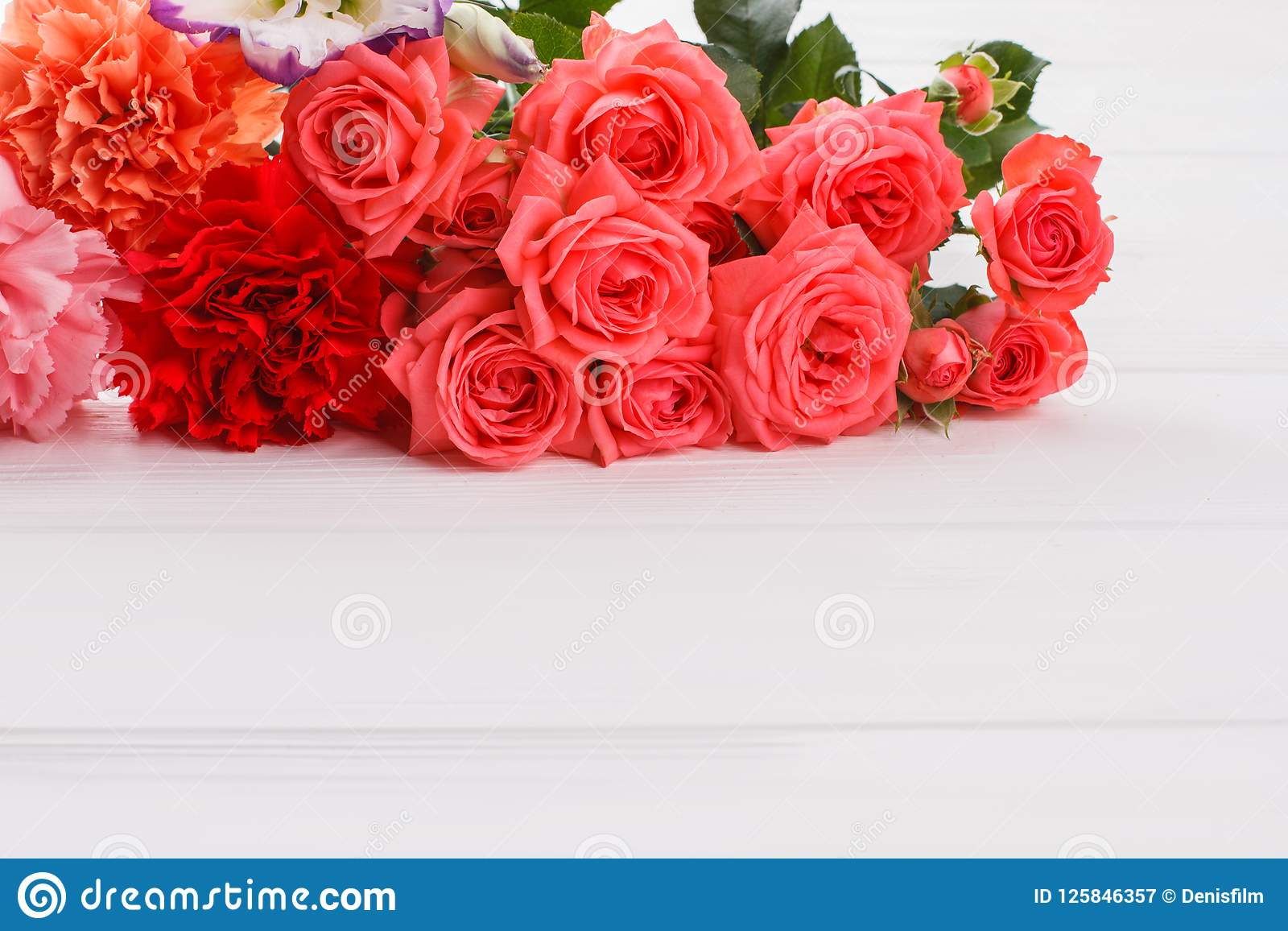 Gartennelke und rosafarbene Blumen auf weißem Holz