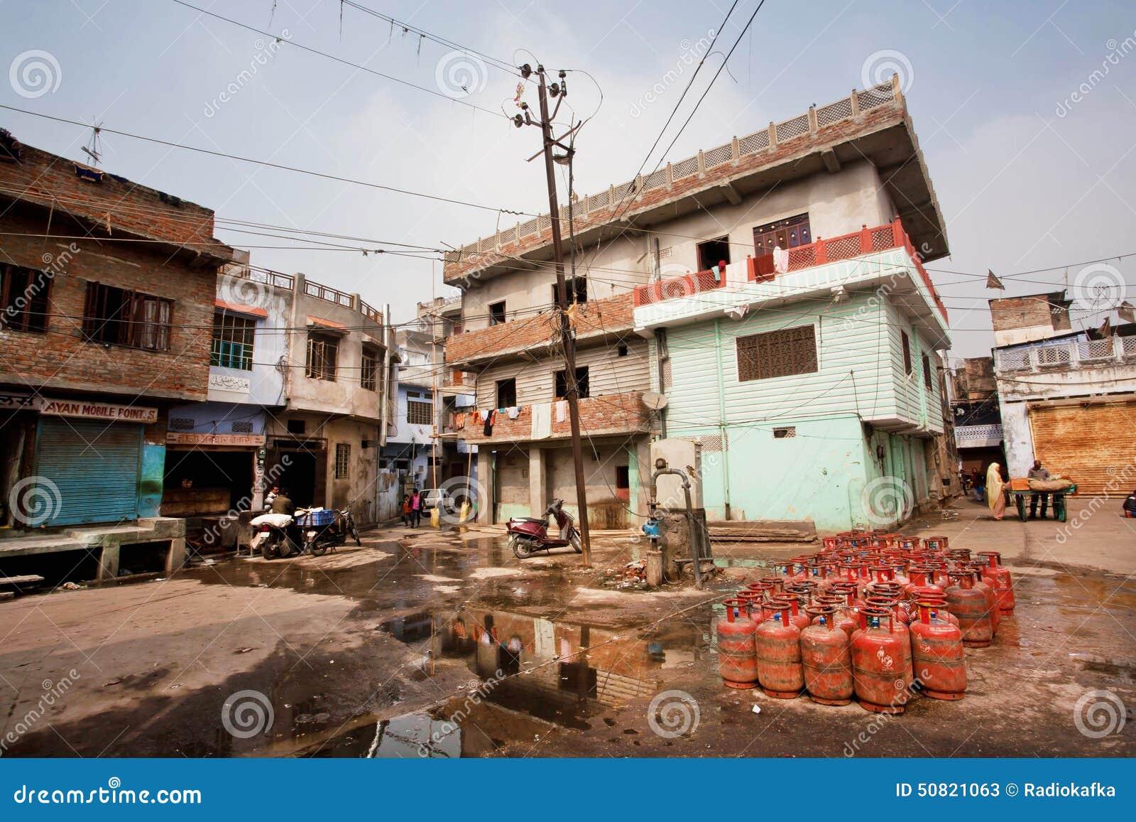 Gasflessen gezet op een vuile straat met oude huizen van slechte families