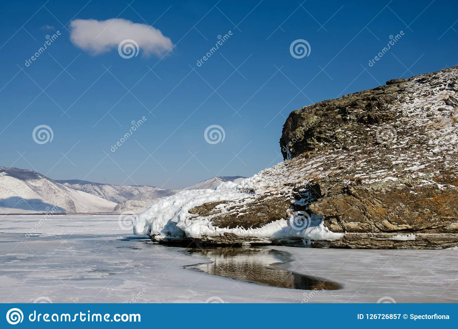 Gat in het ijs van meer Baikal meer dan één meter dik dichtbij rots