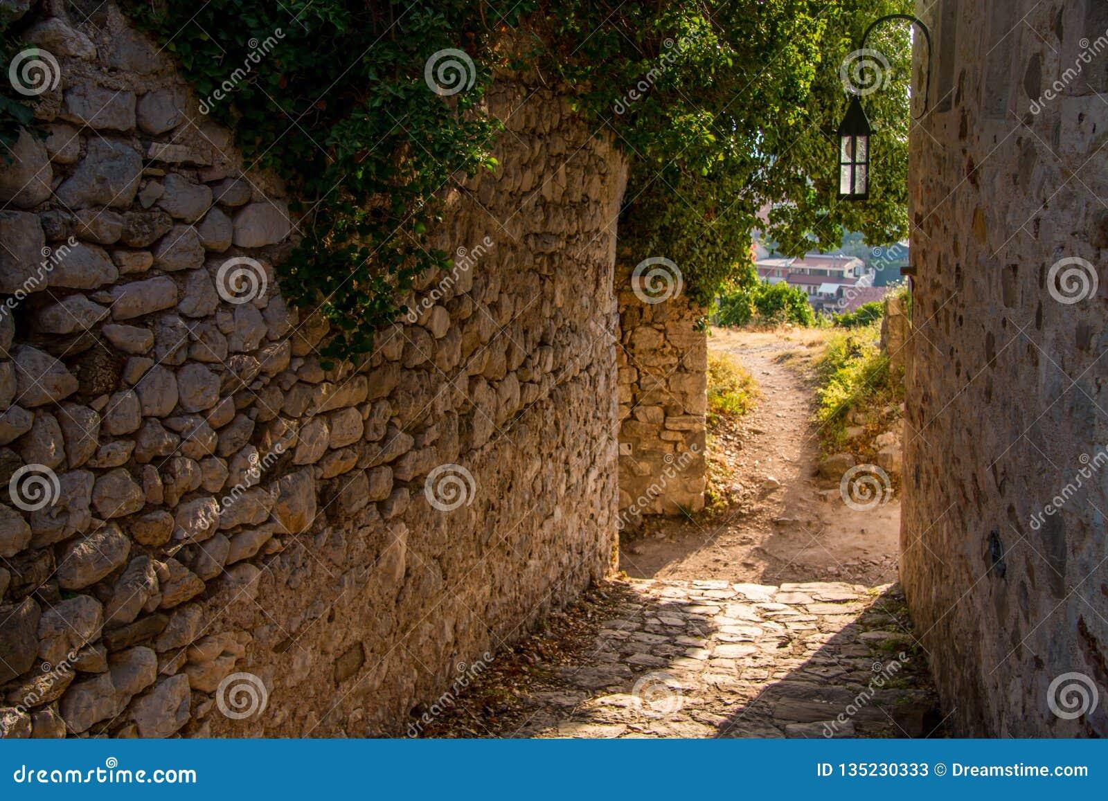 Gata av den gamla staden med solljus på stenbåge