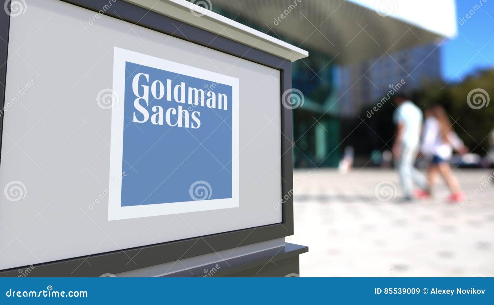 Gatasignagebräde med Goldman Sachs Group, Inc logo Suddig kontorsmitt och gå folkbakgrund