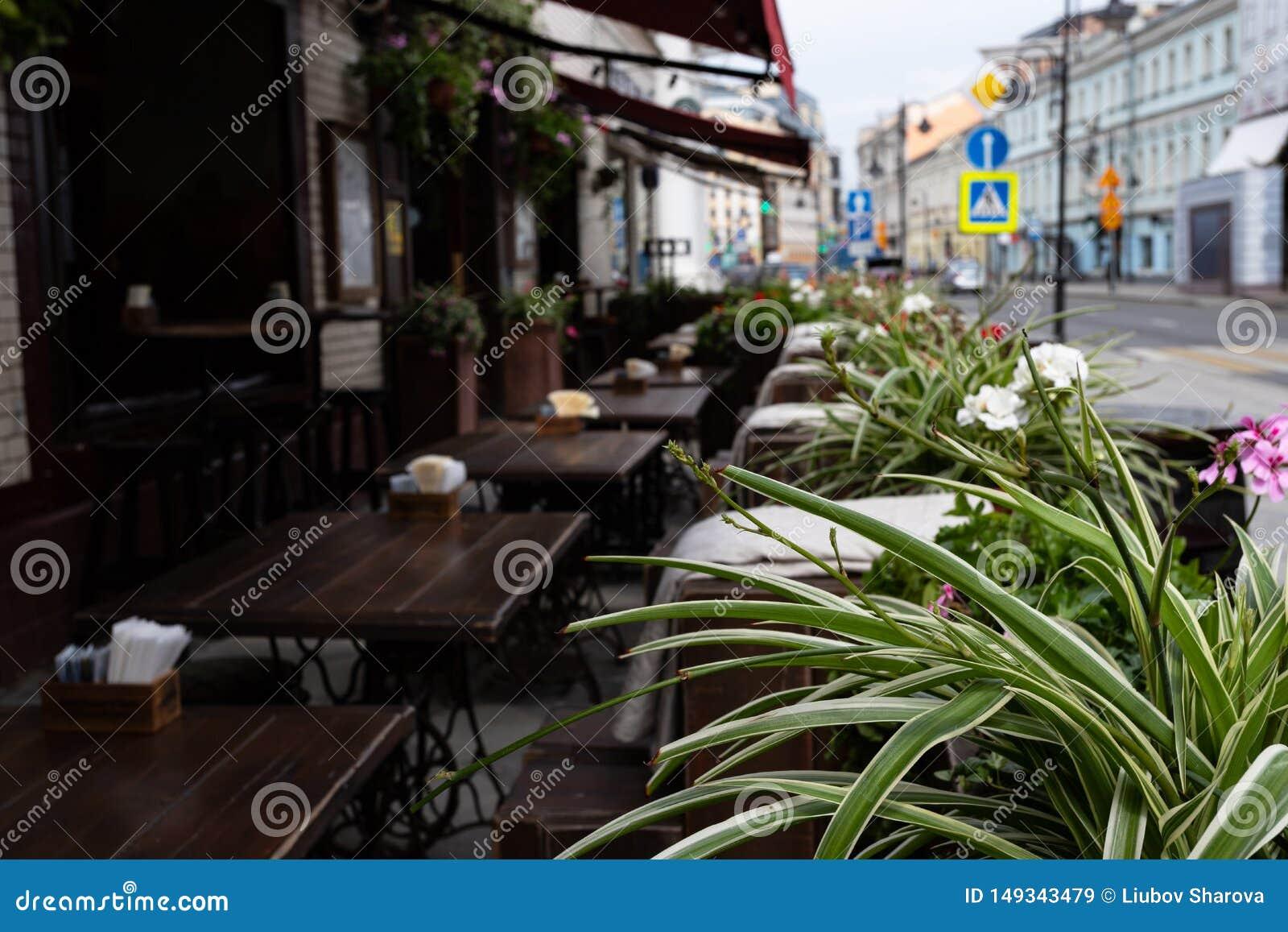 Gatatabeller utanf?r ett kaf? i bakgrunden ?r defocused i f?rgrunden, sidorna av blommor