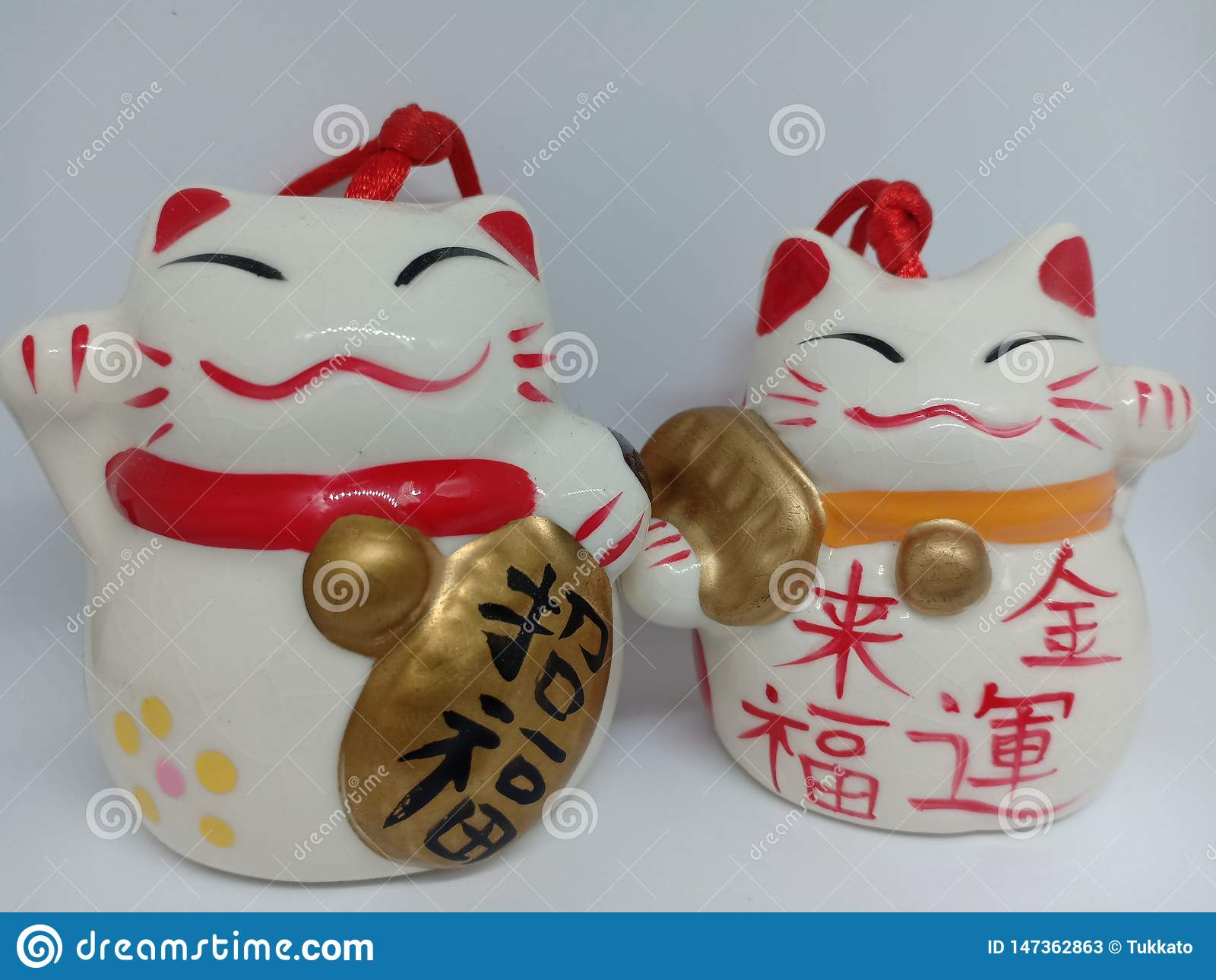 Gatto fortunato giapponese di maneki-neko ceramico su fondo bianco