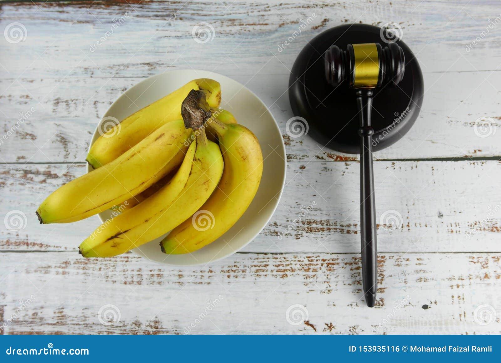 Gavel e casco di banane su fondo di legno Concetto di CAUSA