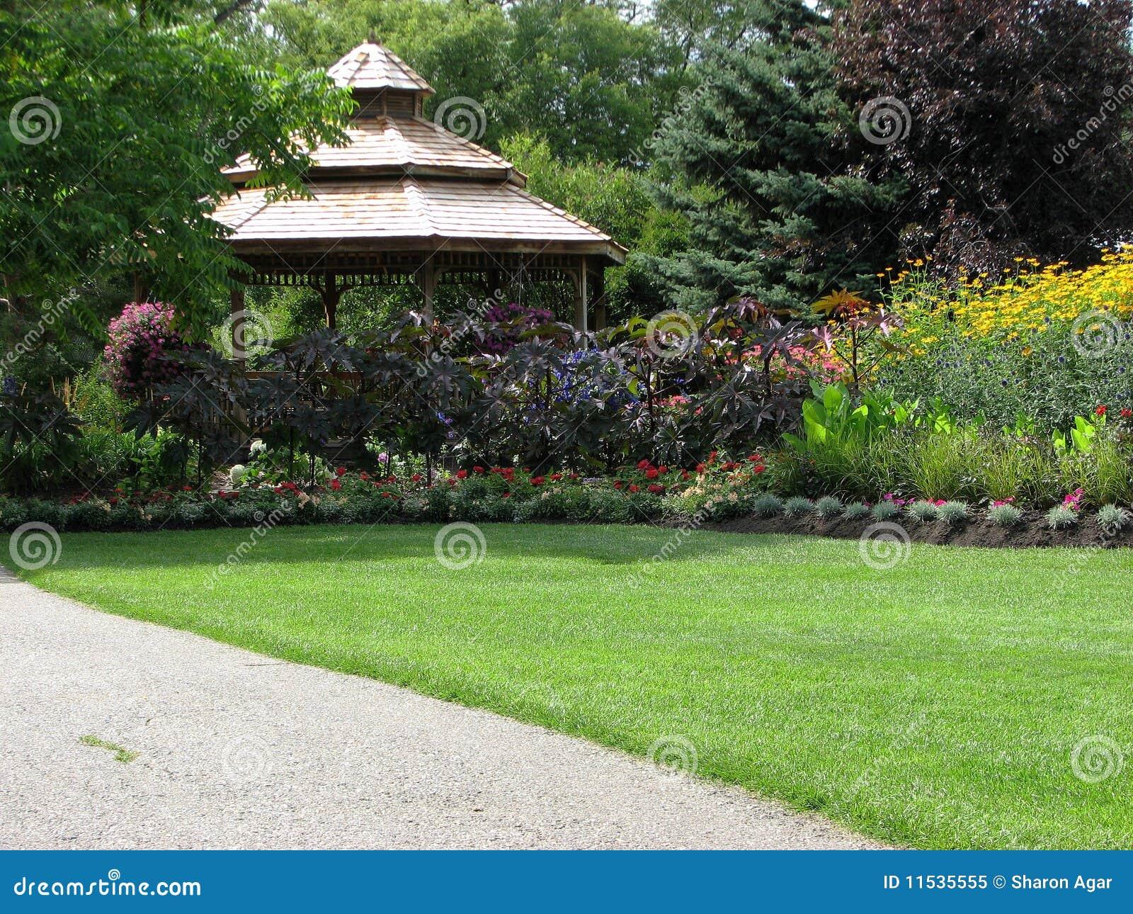 gazebo jardim madeira:Um retrato de um gazebo de madeira do jardim cercado com flores e