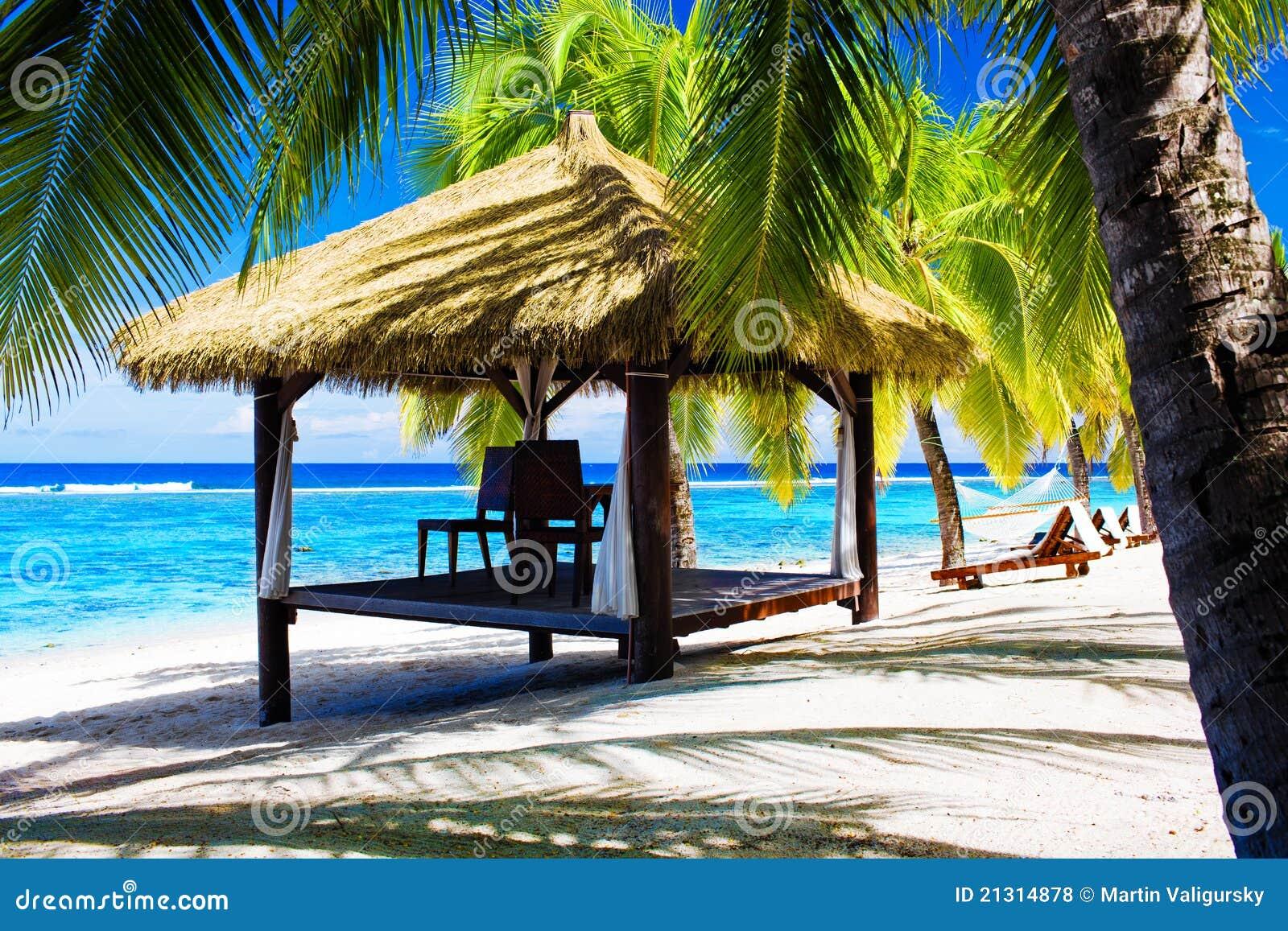 Gazebo tropical con las sillas en una playa