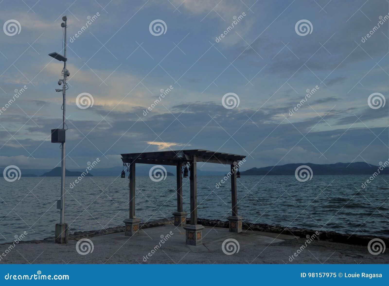 Gazebo vid sjön med telekomantennen bredvid den