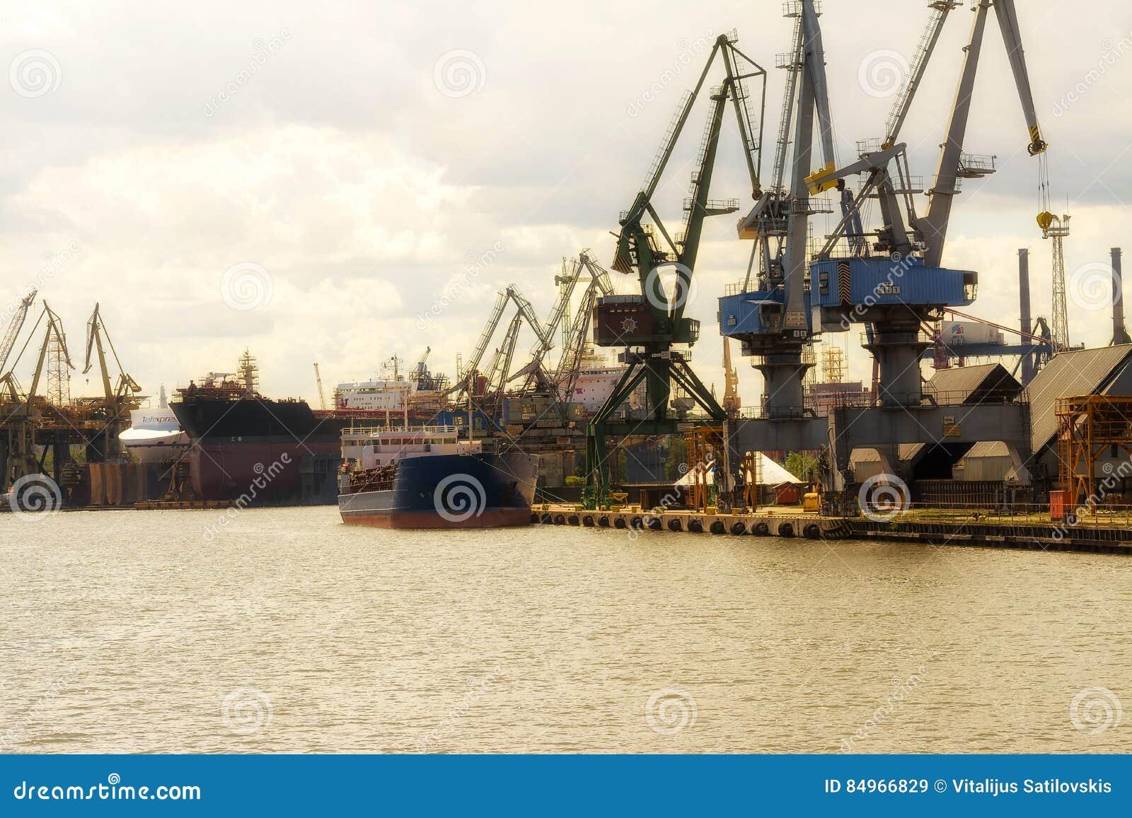 Gdansk, Polonia - 21 de junio de 2016: muchas grúas en fondo, trabajadores, barco de envío