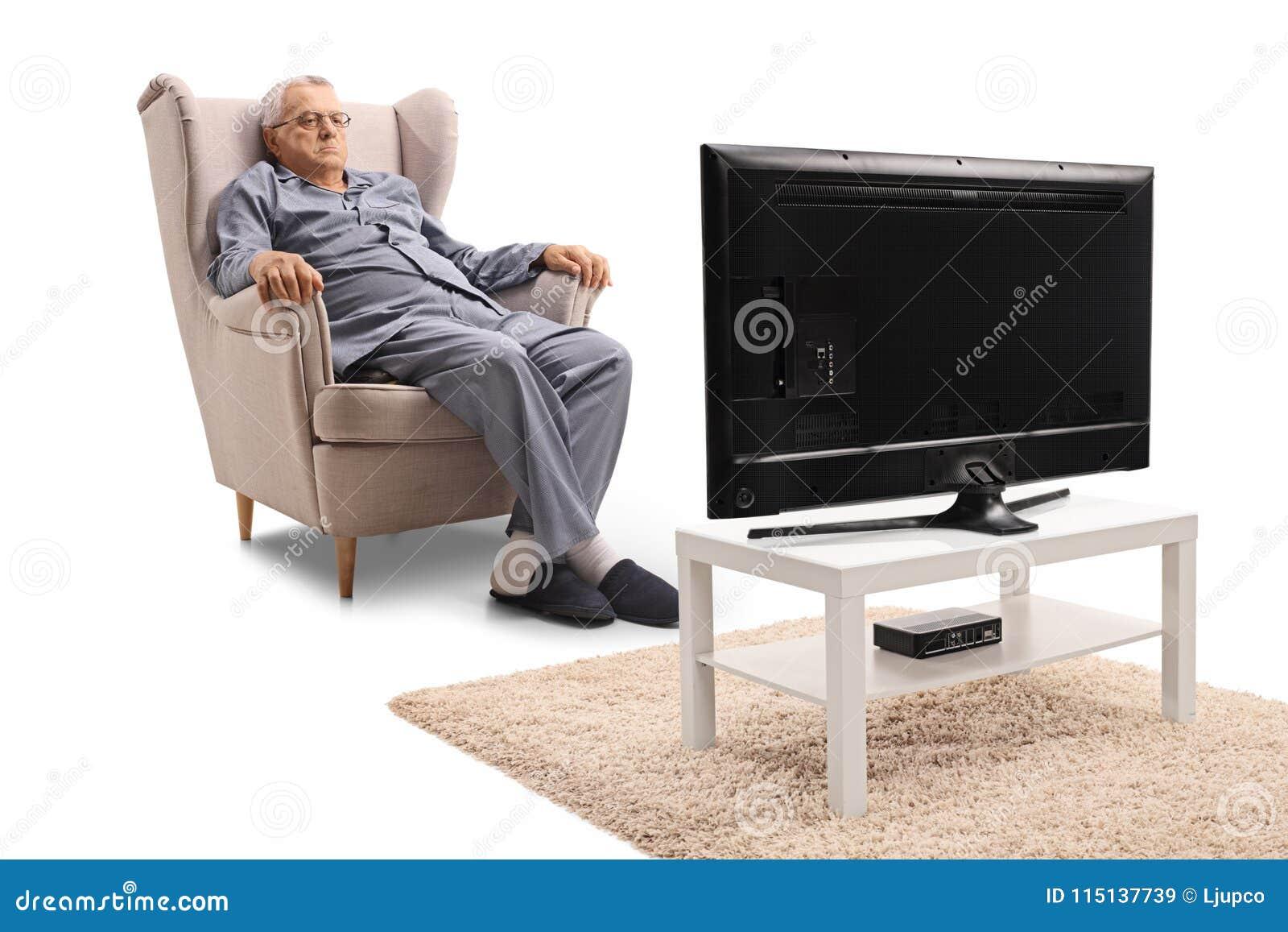 Gderliwy dorośleć mężczyzna siedzi w oglądać i karle w piżamach