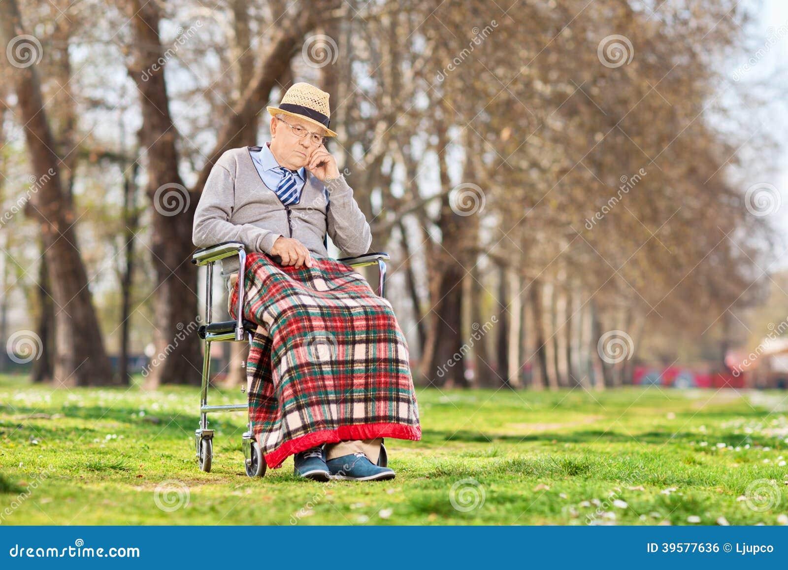 Gderliwy starego człowieka obsiadanie w wózku inwalidzkim w parku