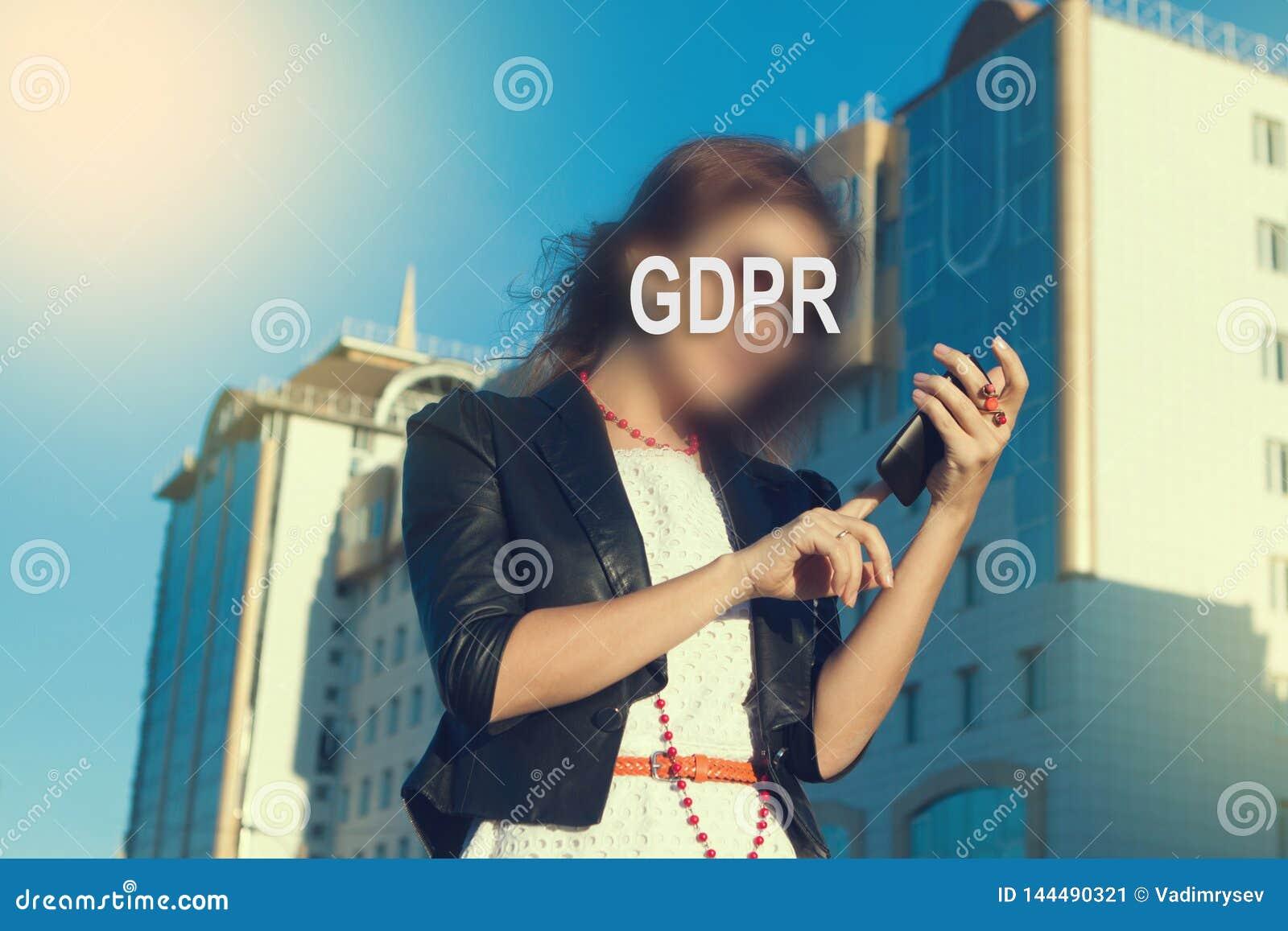GDPR - kobieta chuje jej twarz z inskrypcją GDPR