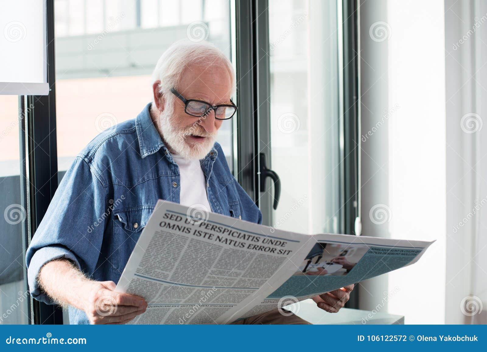Geïmponeerde oude mens die van publicatie thuis genieten