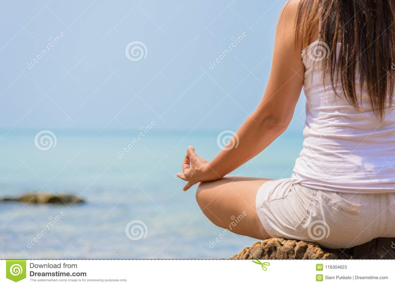 Geïsoleerd op wit De hand van de close-upvrouw het praktizeren de lotusbloem stelt op het strand
