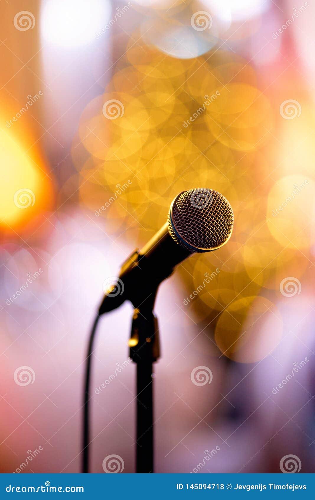 Geïsoleerde bokeh microfoon op een overlegstadium met redy kunstenaars om in de coulisse te presteren