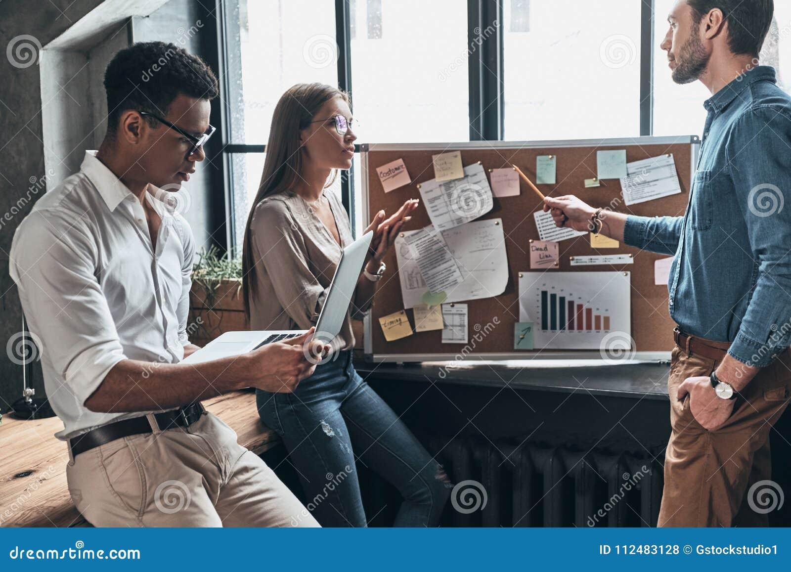 Ge affärsrådgivning Tre unga affärspersoner som använder blackb