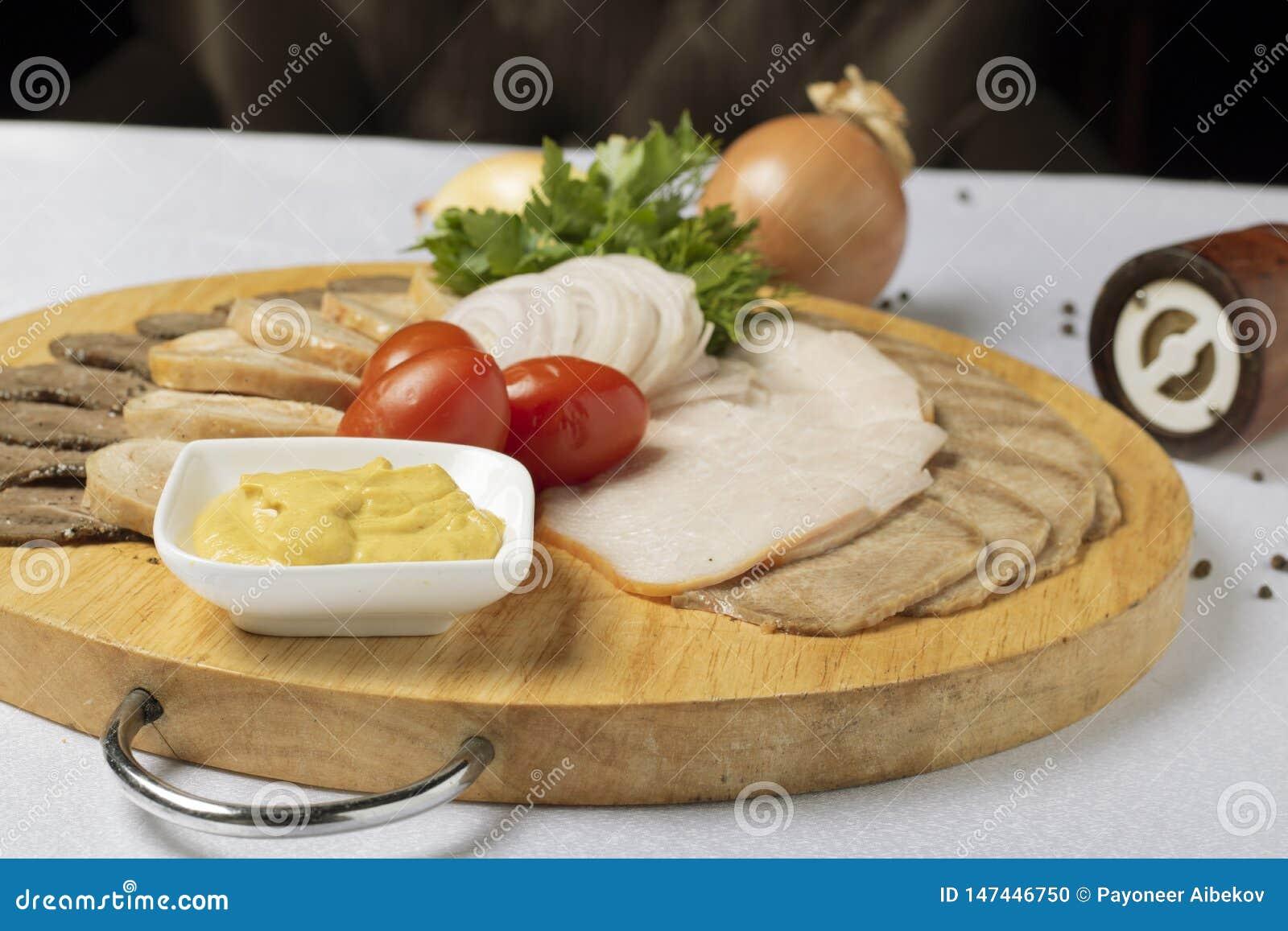 Geassorteerd vlees, kaassaus en kersentomaten met uiringen
