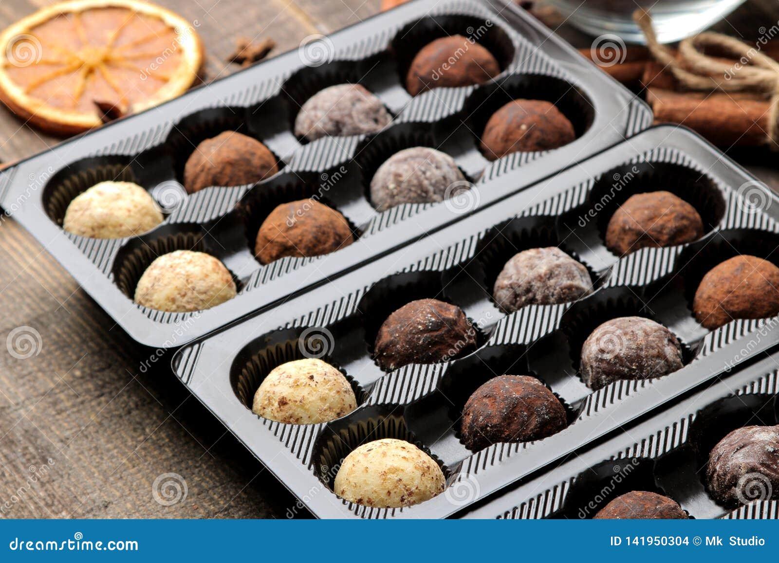 Geassorteerde chocolade Suikergoedballen van verschillende types van chocolade in een vakje op een bruine houten lijst