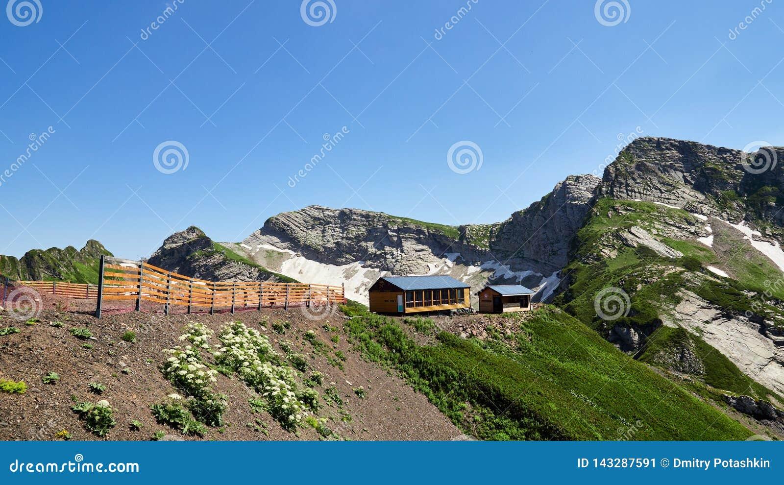 Gebäudebergwachthoch in den Bergen Schnee im Sommer auf den Steigungen der Berge
