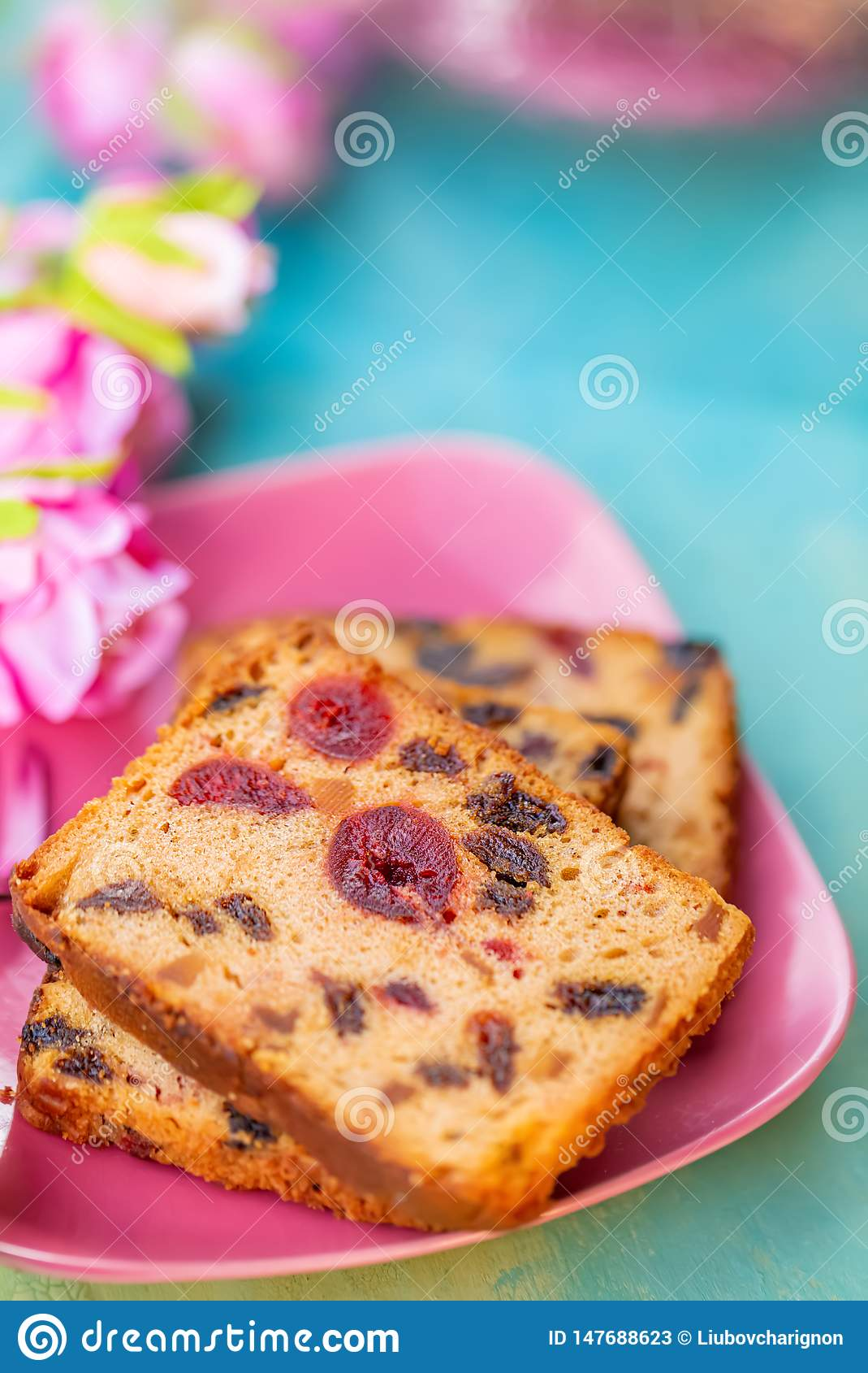 Geb?ck Eine Kuchenscheibe mit Fr?chten auf einer rosa Platte Fruchtkuchenrosine und -kirsche