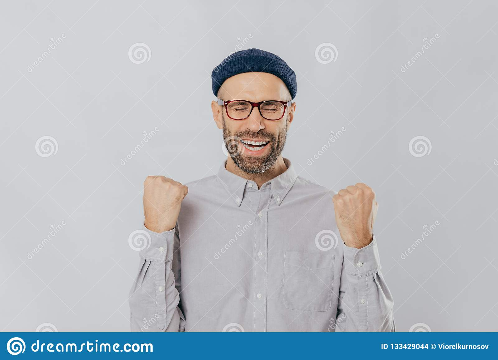 Gebaar van succes Jubilant extatische ongeschoren mens heft dichtgeklemde vuisten op, draagt bril en het formele overhemd, viert