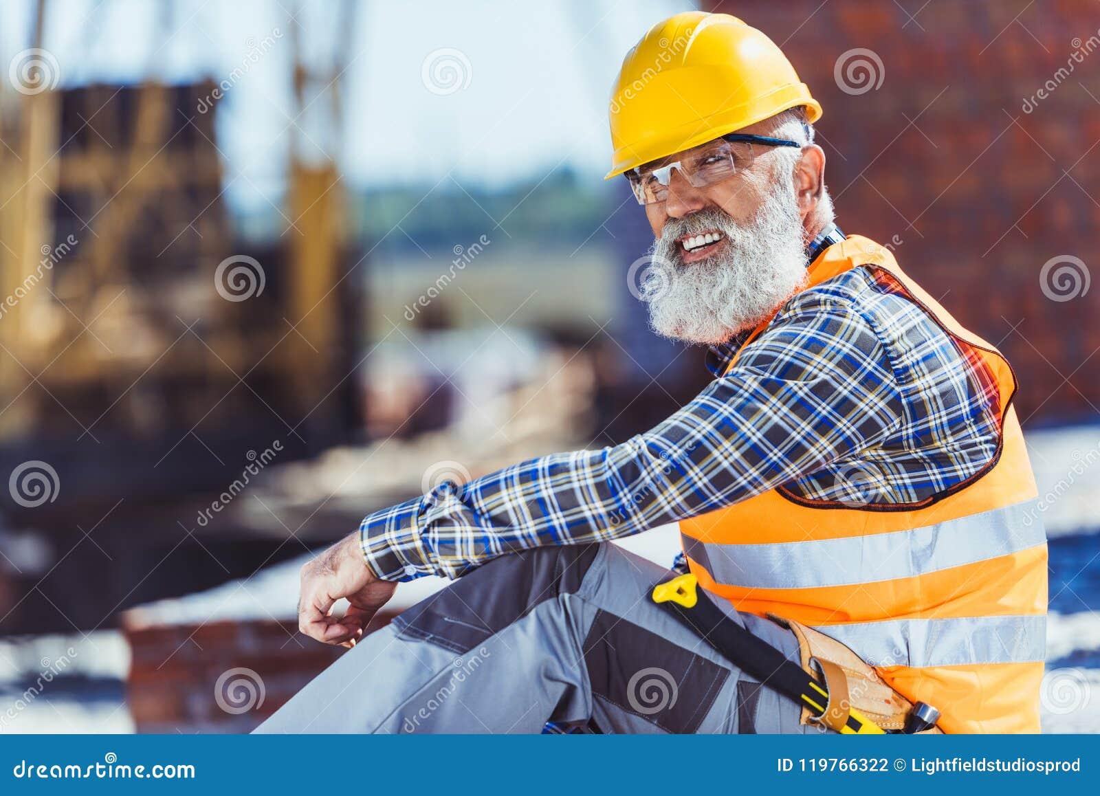 Gebaarde arbeider in weerspiegelende vest en bouwvakkerzitting bij bouwwerf en het kijken