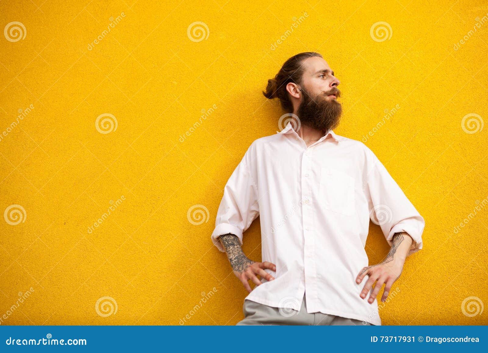 Gebaarde hipster op gele uitstekende muur