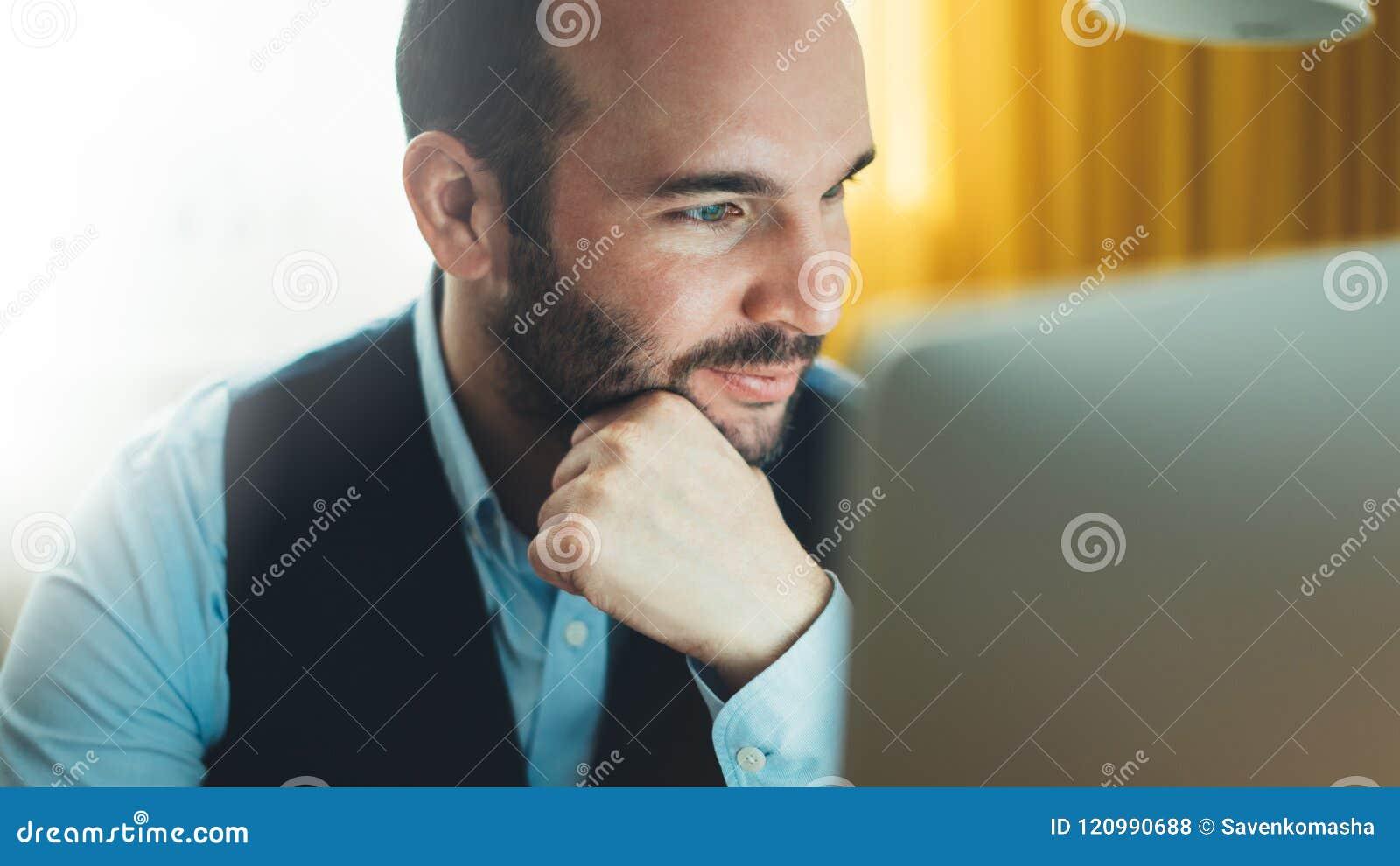 Gebaarde jonge zakenman die aan modern bureau bij nacht werken Adviseurmens die het kijken in monitorcomputer denken Manager die