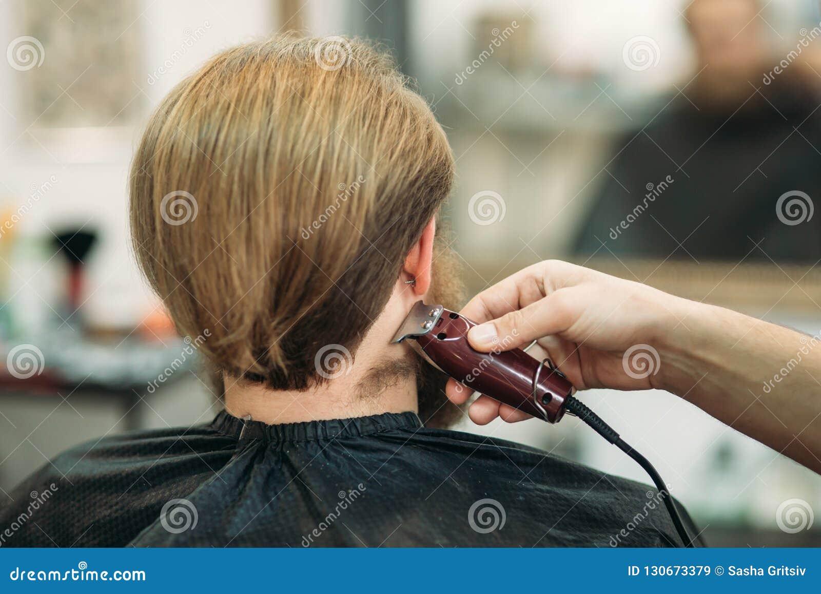 Gebaarde mens die een kapsel met een haarclippers hebben Achter mening