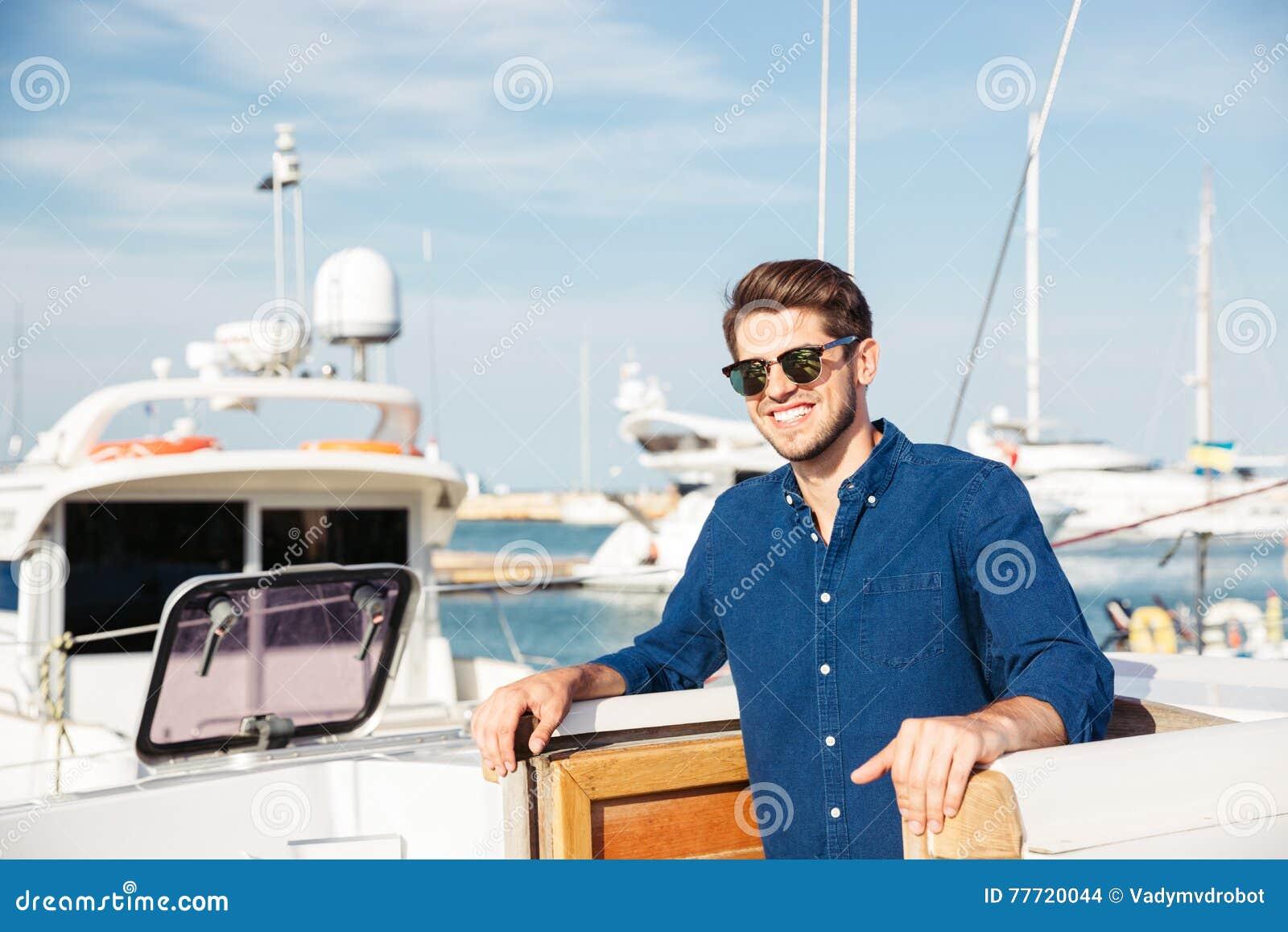 Gebaarde mens die zonnebril dragen en zich op een jacht bevinden