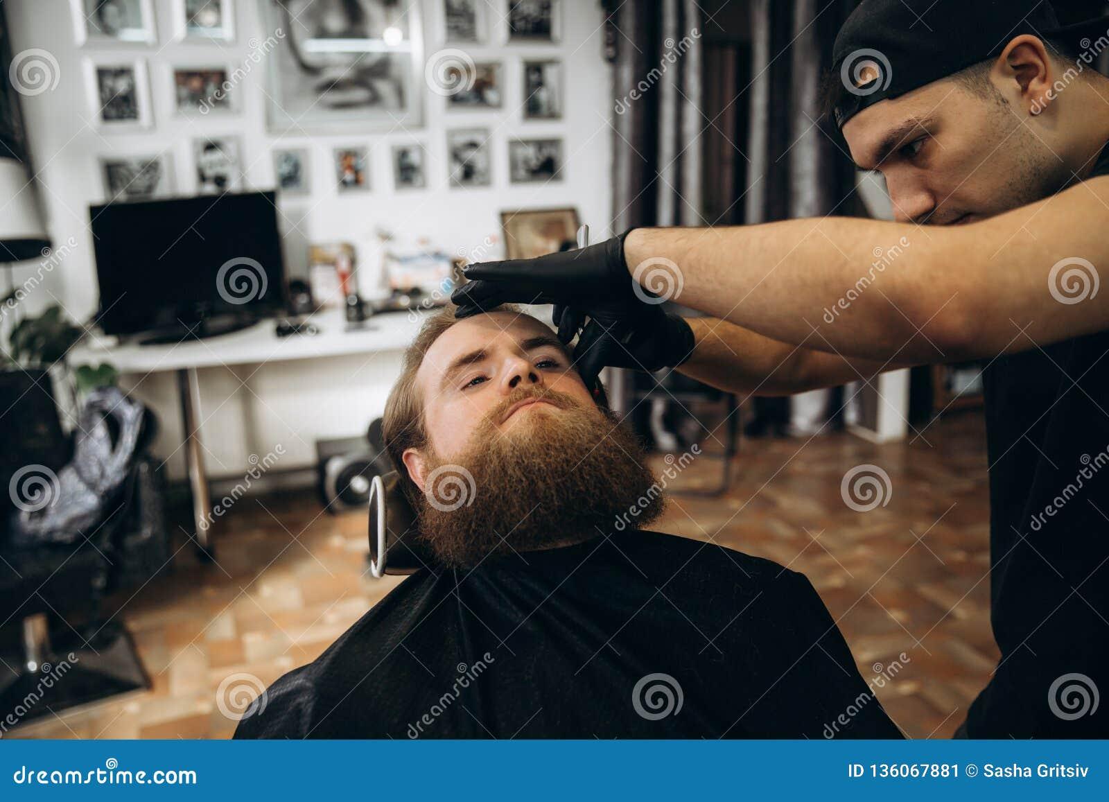 Gebaarde mens met lange baard die het modieuze haar scheren, kapsel, met scheermes krijgen door kapper in herenkapper