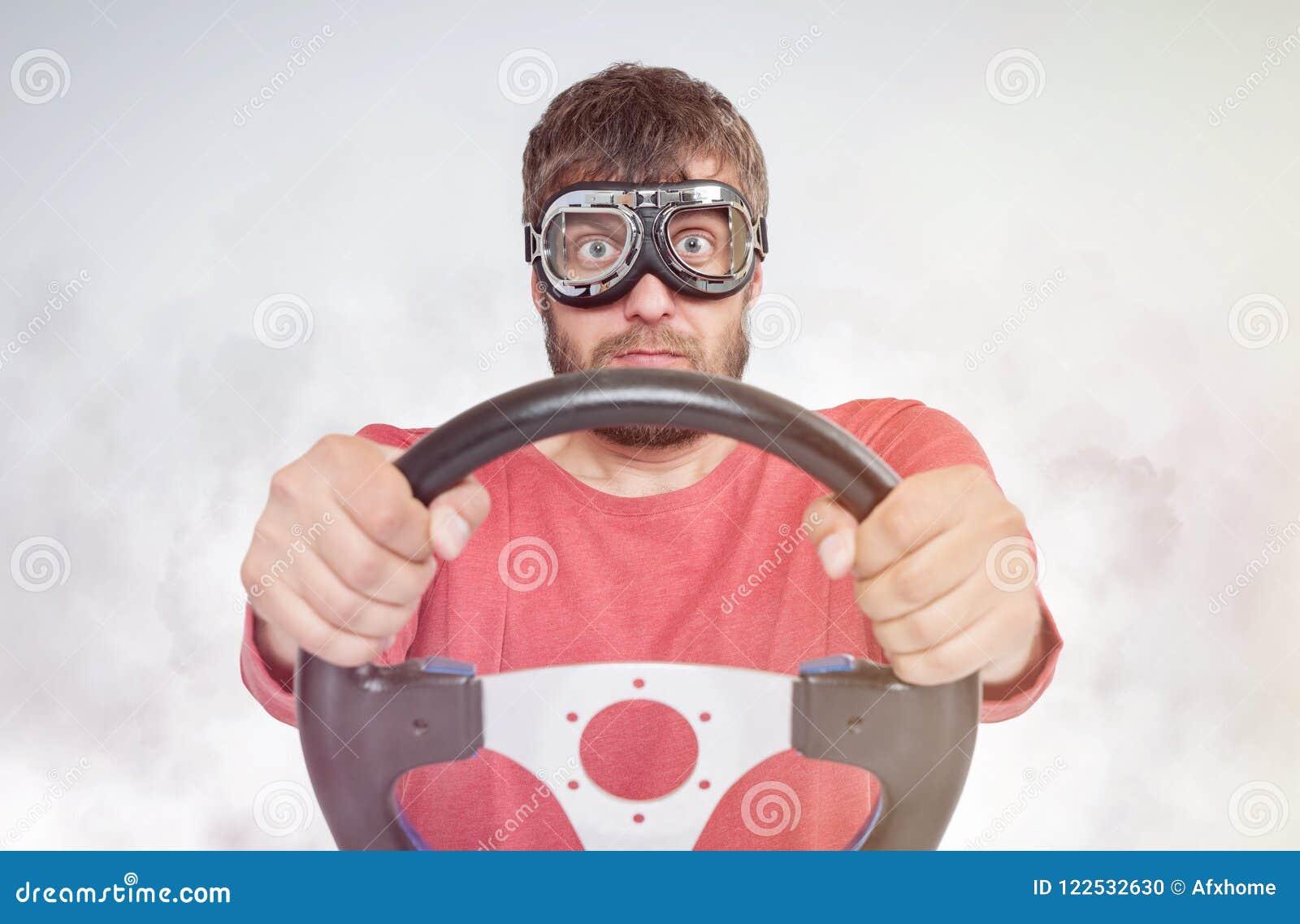 Gebaarde mens in modieuze beschermende brillen met stuurwiel op rookachtergrond, het concept van de autobestuurder