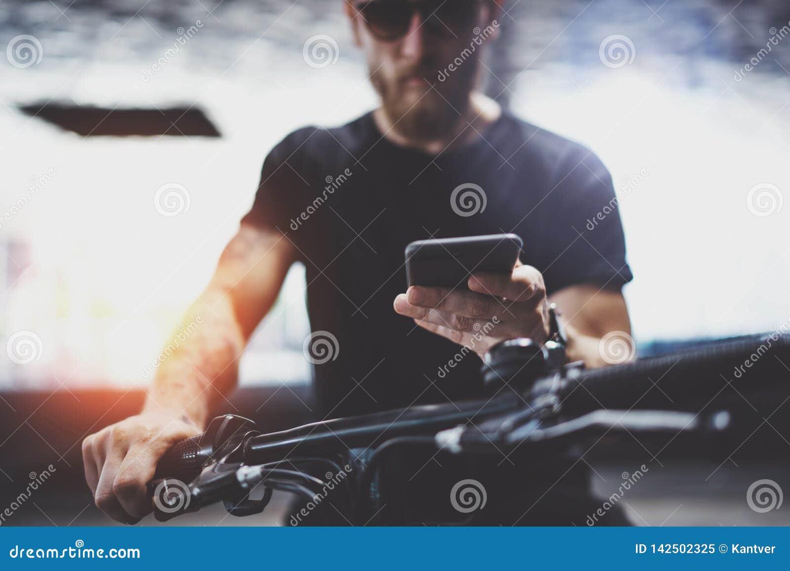 Gebaarde spier getatoeeerd hipster in zonnebril die smartphone na het berijden gebruiken door elektrische autoped in de stad