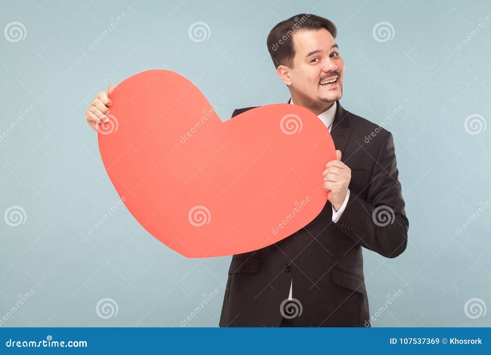 Gebaarde zakenman die groot rood hart en het toothy glimlachen houden