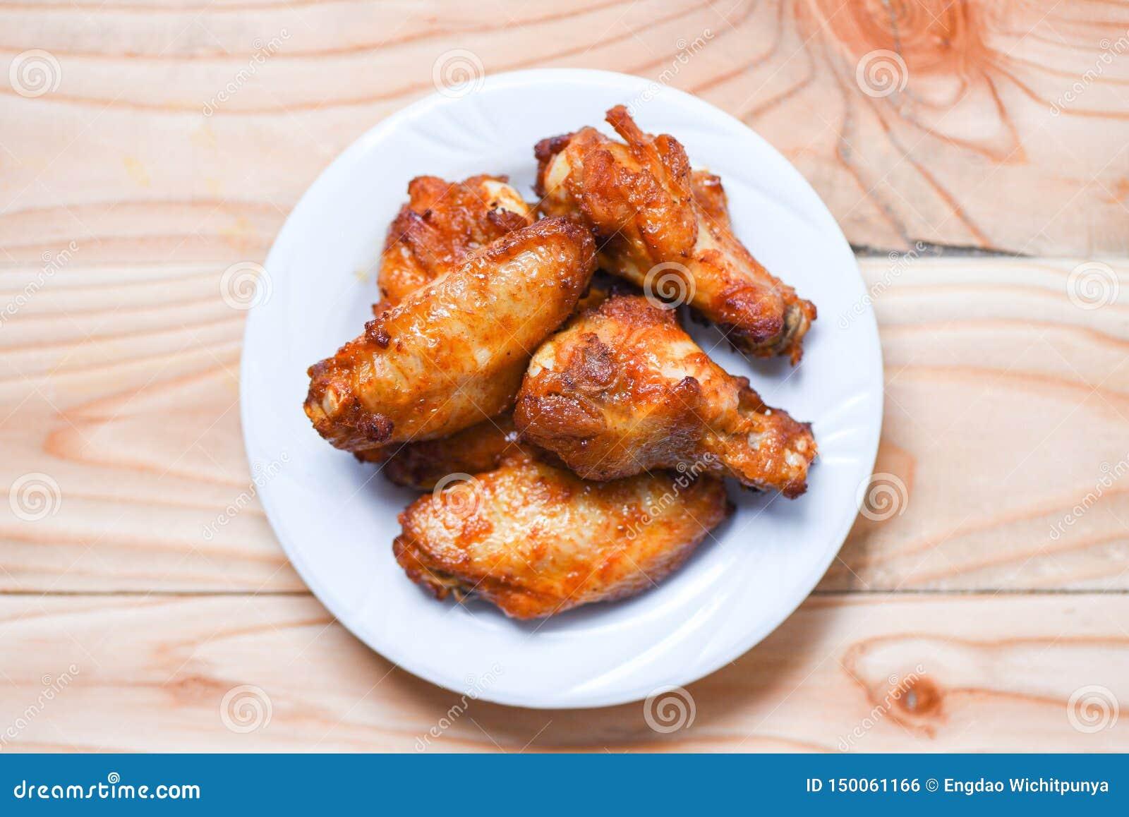 Gebackener Hühnerflügel bbq-Grill auf des Tabellen-Hintergrundes der Platte hölzernem heißem und würzigem Huhn - und Soße