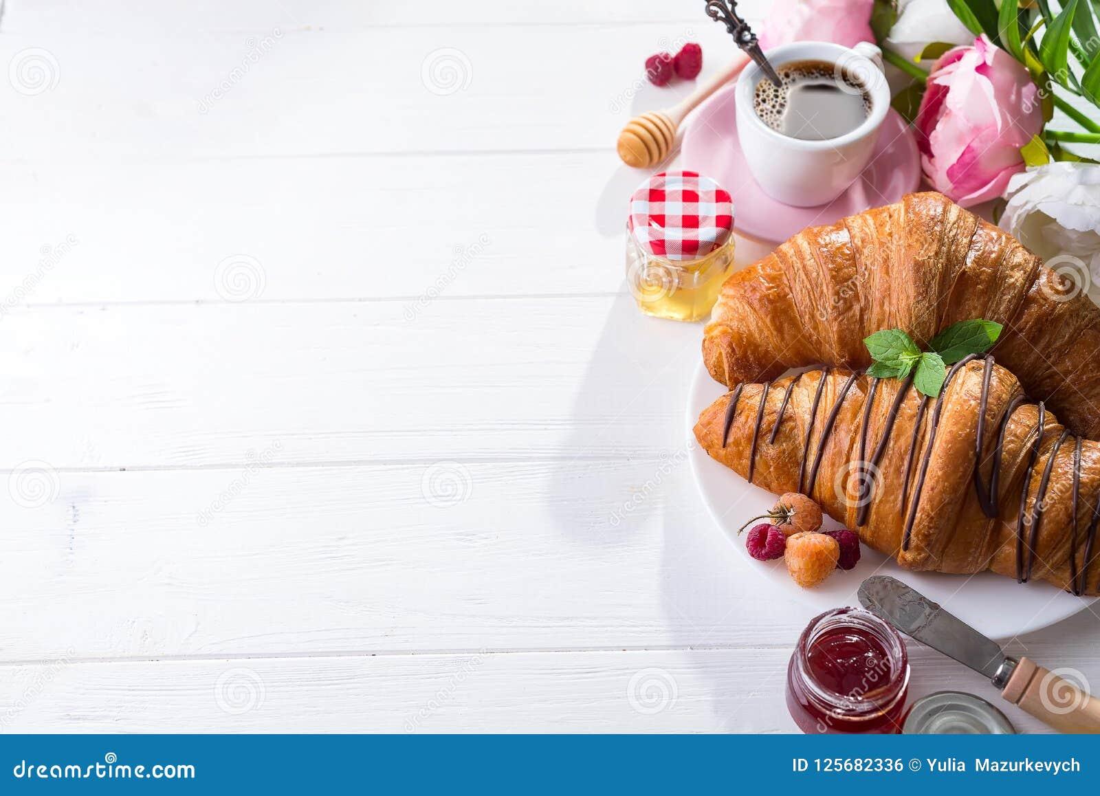 Gebackenes Hörnchen des Frühstücks frisch verziert mit Stau und Schokolade, Blumen auf Holztisch in einer Küche mit Kopienraum