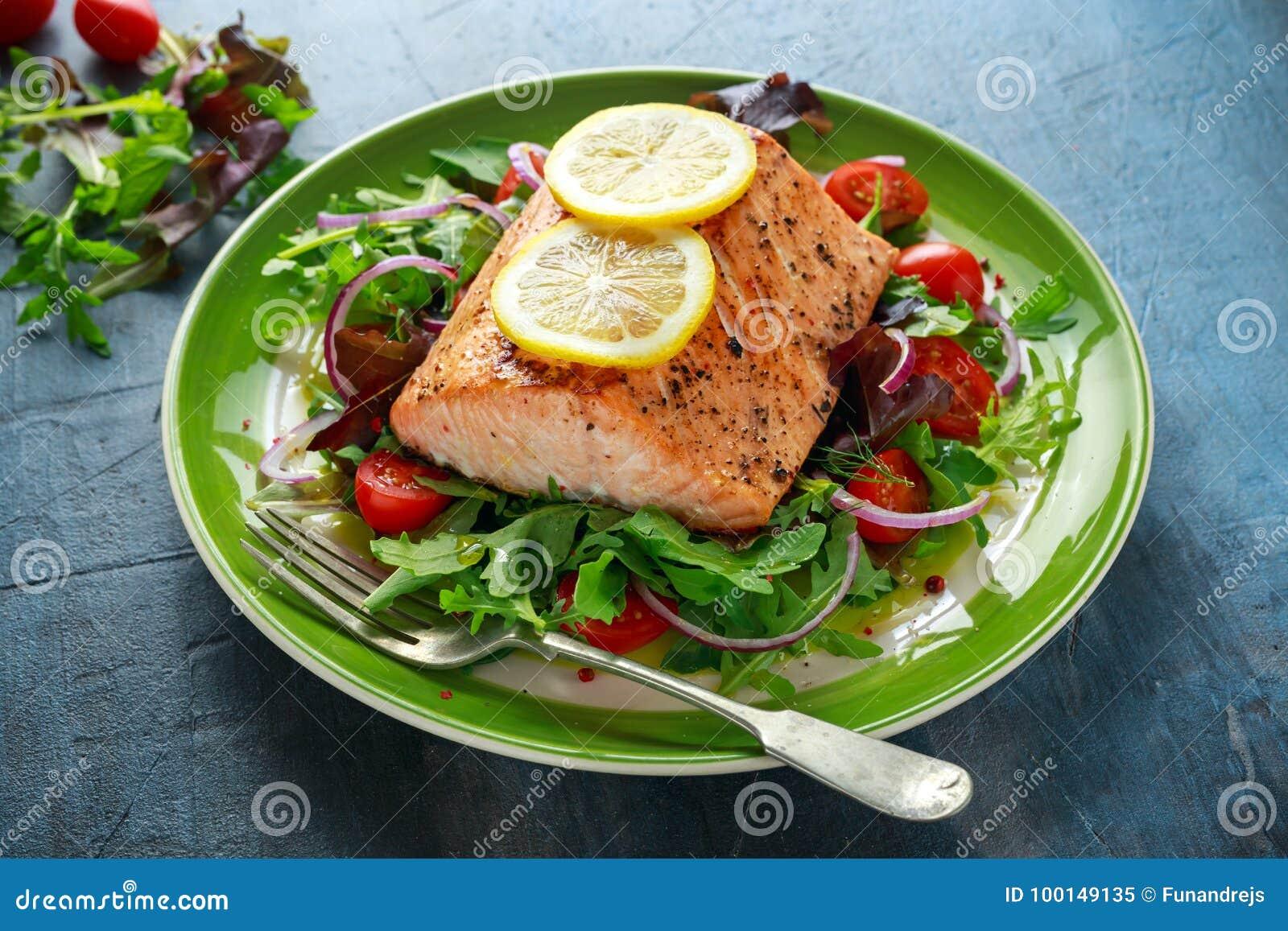 Gebackenes Lachssteak mit Tomate, Zwiebel, Mischung des Grüns lässt Salat in einer Platte Gesunde Nahrung
