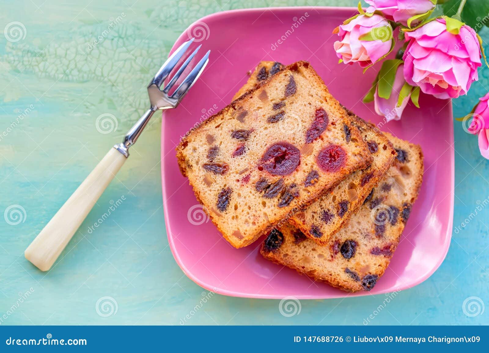Gebakjes Een cakeplak met vruchten op een roze plaat De rozijn en de kers van de fruitcake