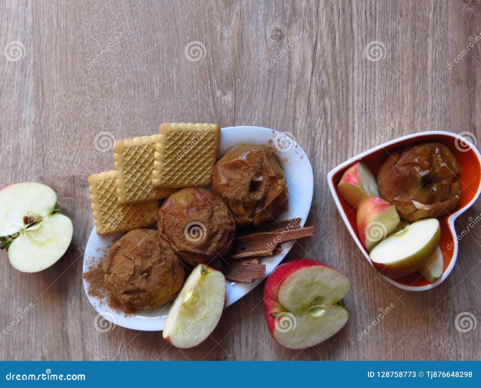 Gebakken en fress appelen, koekjes, en kaneel op de rustieke achtergrond van het stijl eiken hout Licht bio organisch ontbijt