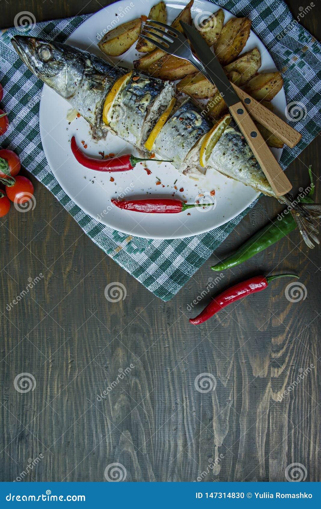 Gebakken makreel met citroen en aardappelen in de schil op een witte plaat Verse product-groenten vegetables Kers, Spaanse peperp