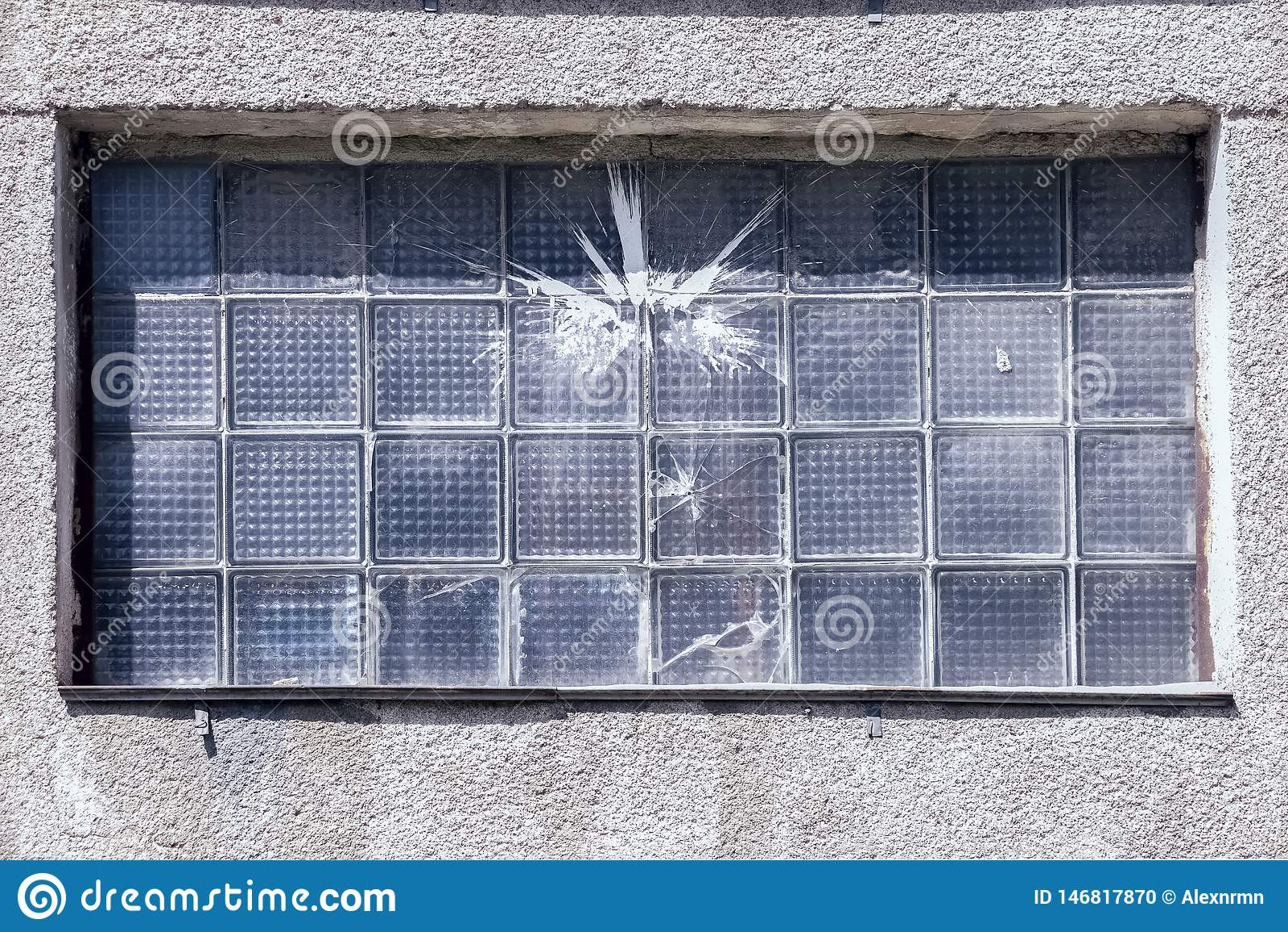 Gebarsten venster na het werpen van stenen en verf