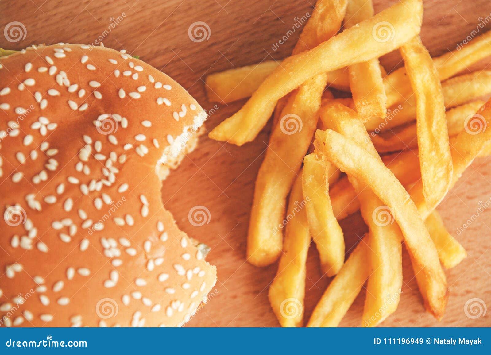 Gebeten Hamburger en Frieten op een houten Raad