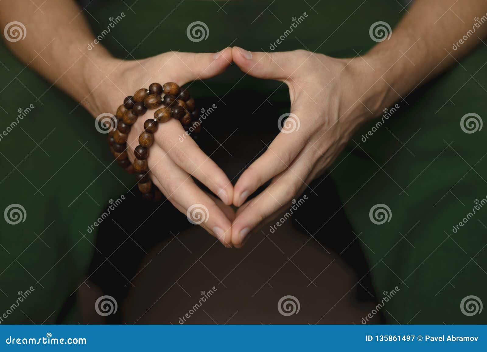 Gebetsperlen für Meditation in den Händen der Männer Frieden, Bewusstsein und Mindfulness