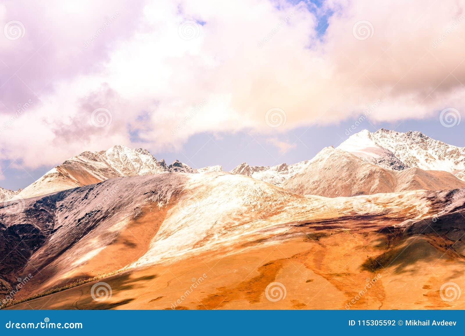 Gebirgszug mit schneebedeckten Spitzen unter den Wolken