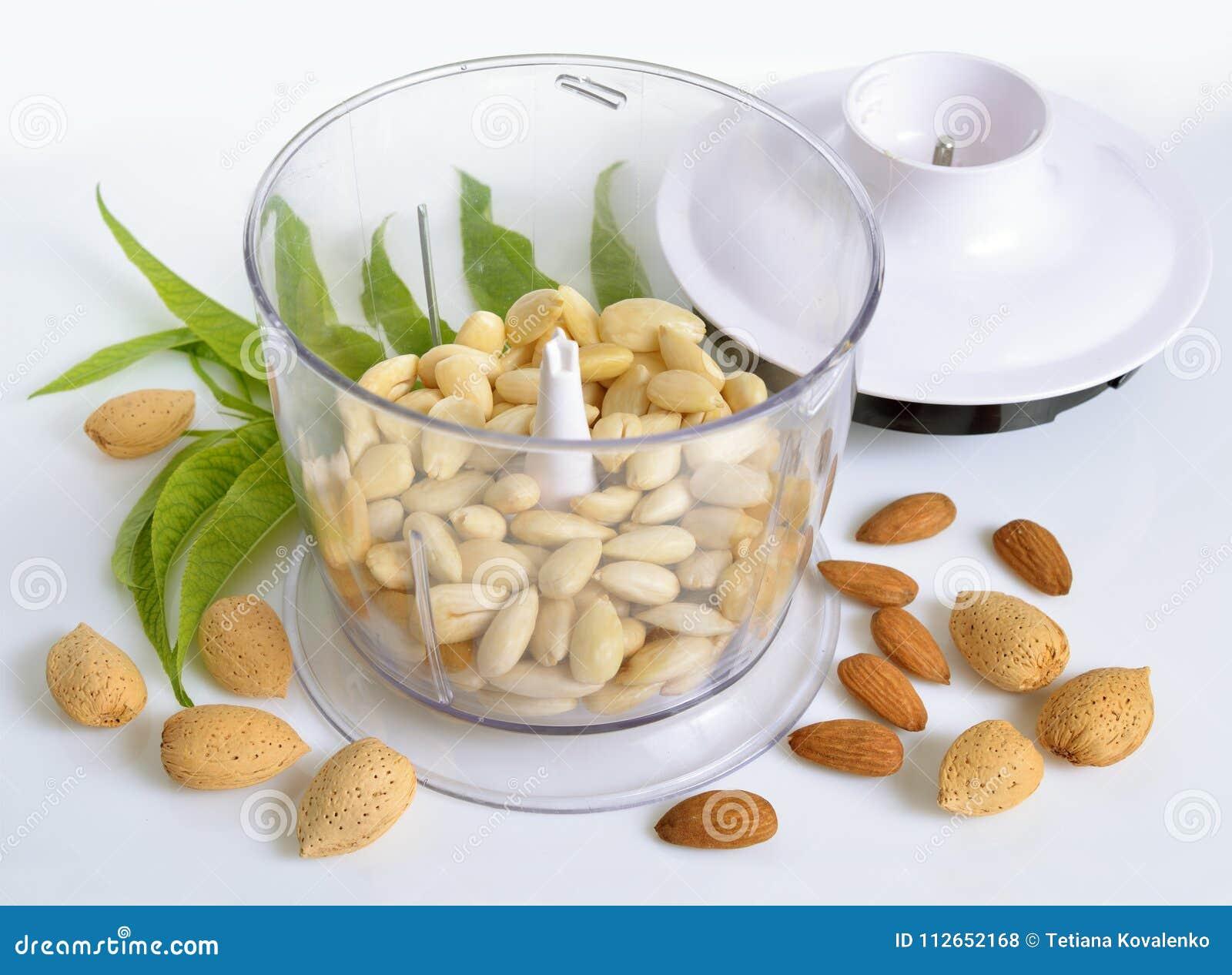 Geblichene Mandeln in einer Mischmaschine mit ungeschälten Nüssen Auf Weißrückseite